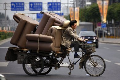 while-in-beijing-a-man-bikes-around-with-a-lot-of-furniture